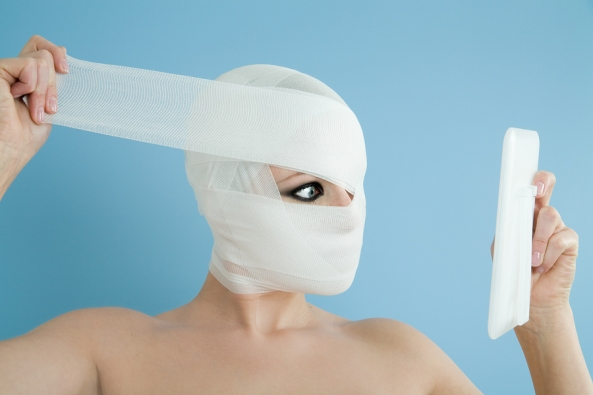 Plastic surgery concept on blue background with woman opening bandages in front of mirror.